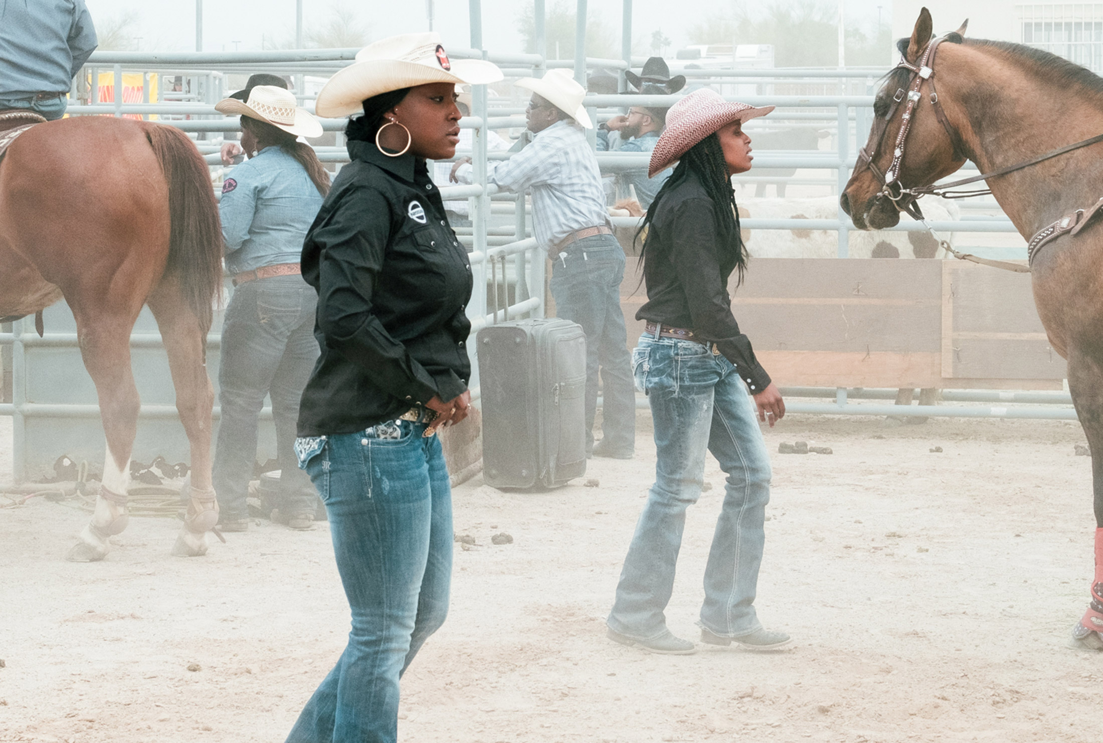 Two women with cowboy hats standing next to horses outdoors in a rodeo arena